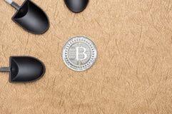 Crypto bitcoins τοπ άποψης ασημένιο νόμισμα πέρα από τη μαύρη μεταλλεία φτυαριών επάνω Στοκ Εικόνα