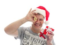 Crypto Christmas - Man with Bitcoin. Sydney, Australia - December 17, 2017;  Man holding a Bitcoin - digital crypto currency and some small presents at Christmas Royalty Free Stock Images