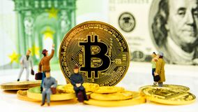 Crypto currencies, bitcoin especially is the possibility to get rich. Closeup of golden bitcoin coin on dollar banknote background with many golden coins at Stock Photos