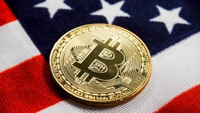 Crypto currency bitcoin against usa flag. Crypto currency bitcoin btc golden bit coin against flag of United States of America USA. Virtual money, blockchain stock image