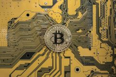 Crypto currency bitcoin. Bitcoin coin on exchange charts. e-currency bitcoin on the background of the circuit board royalty free stock image