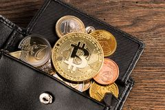 Crypto currency bitcoin euro wallet concept wooden background. Golden bitcoin crypto currency coin on euro coins in leather wallet on wooden background royalty free stock image