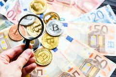 Crypto currency Bitcoin trough magnifying glass on real traditional euros background. investment, business,. Risk concept stock photo