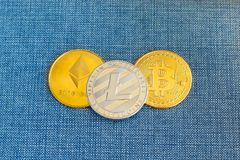 Crypto currency coin Bitcoin, Litecoin and Ethereum coins in leather wallet on blue background. Cryptocurrency concept royalty free stock images