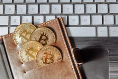 Crypto currency coins in leather wallet on the laptop keyboard. stock photo