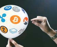 Crypto currency concept - bit coin BTC the new virtual money on. Balloon with needle in hand before burst Royalty Free Stock Images