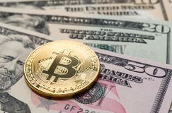 A bitcoin with dollar bills Royalty Free Stock Images