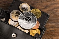Crypto currency ethereum euro wallet concept wooden background. Silver ethereum crypto currency coin on euro coins in leather wallet on wooden background Stock Photos