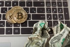 Gold bitcoins and crumpled dollars on laptop Royalty Free Stock Photography