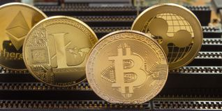 Crypto currency gold coins on a motherboard. On a motherboard in slots are standing gold coins of a digital crypto currencies - litecoin bitcoin ripple royalty free stock image