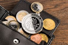Crypto currency iota wallet euro concept wooden background. Silver iota crypto currency coin on euro coins in leather wallet on wooden background Royalty Free Stock Images