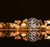 Crypto currency litecoin on the background of gold bars royalty free stock photos
