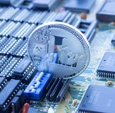Crypto currency litecoin on printed circuit board. On a printed circuit motherboard is standing silver coin of a digital crypto  currency - Litecoin. The switch Stock Photos