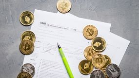 Crypto currency: Pages of the tax form 1040 and a scatter of coins bitcoin, ethereum. Top view stock image
