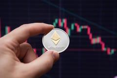 Crypto muntetherium ethereummuntstuk op uitwisselingsgrafieken e-munt etherium op de achtergrond van het programma stock afbeelding
