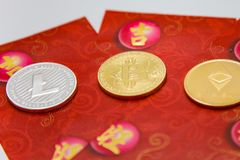 Crypto Red Packets. Crypto currency coins on top of traditional red envelope gift packets Stock Photo