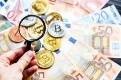 Crypto waluty Bitcoin synkliny powiększać - szkło na istnym tradycyjnym euro tle inwestycja, biznes, zdjęcie stock
