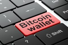 Cryptocurrency概念:在键盘背景的Bitcoin钱包 库存图片