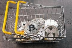 Cryptocurrency购物清单概念,各种各样在手提篮的银色和金黄物理数字隐藏金钱硬币 库存照片