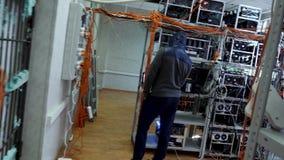 Cryptocurrency-Ausr?stung, Mann in der Sportklagenstellung vor dem Bergbauelektronischen Bauernhof des geldes, Finanzkonzept stock footage