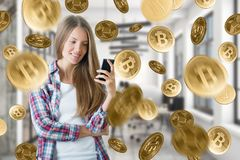 Cryptocurrency and banking concept. Attractive smiling young woman using smartphone on abstract blurry interior background with golden bitcoin rain Royalty Free Stock Image