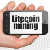 Cryptocurrency begrepp: Räcka hållande Smartphone med Litecoin som bryter på skärm Royaltyfri Fotografi