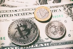 Cryptocurrency bitcoin coin near one dollar coin and one euro coin on dollar banknote. Symbol of crypto currency - electronic virt Royalty Free Stock Images
