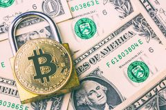 Cryptocurrency bitcoin coin on padlock and many american dollar banknotes. Symbol of crypto currency - electronic virtual money fo. R web banking and Stock Photo