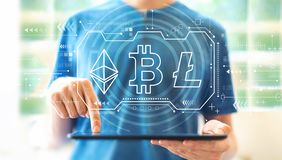 Cryptocurrency - Bitcoin, Ethereum, Litecoin with man using a tablet royalty free stock photo