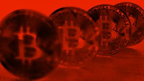 4 Bitcoins with focus on fourth coin back in a red tint stock image