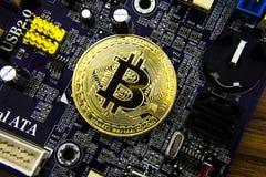 Cryptocurrency Bitcoin sulla scheda madre Moneta di oro Valuta virtuale Immagine Stock
