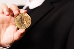 Cryptocurrency Bitcoin. Women hold the cryptocurrency coin on hand. Physical bitcoins gold coin stock images