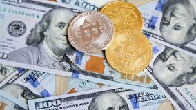 Cryptocurrency Bitcoins вращая на 100 долларах банкнот видеоматериал
