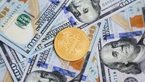 Cryptocurrency Bitcoins вращая на 100 долларах банкнот акции видеоматериалы
