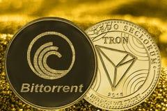 Cryptocurrency BTT и TRX монеток на золотой предпосылке стоковое изображение rf