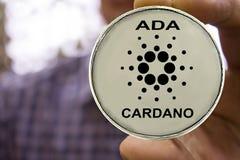 Cryptocurrency Cardano dans la main du ` s d'homme photographie stock