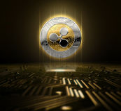 Cryptocurrency And Circuit Board. A ripple cryptocurrency hologram in gold and silver physical coin form hovvering over a computer circuit board- 3D render Stock Images