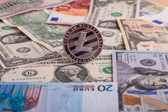 Cryptocurrency coin Litycoin on the euro and dollar banknotes. Financial concept of virtual money.  Stock Image