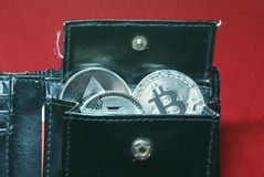 Cryptocurrency coins in a black leather wallet stock photo