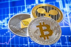 Cryptocurrency coins over trading graphic screen; Bitcoin, Ether. Eum and Ripple coins royalty free stock images