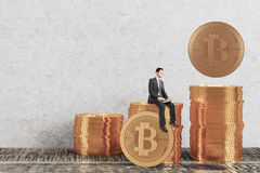 Cryptocurrency concept. Businessman sitting on golden bitcoin piles in interior and using laptop. Cryptocurrency concept. 3D Rendering Stock Photo