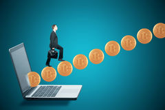 Cryptocurrency concept. Side view of young businessman climbing abstract bitcoin ladder on blue laptop background. Cryptocurrency concept. 3D Rendering Stock Photography