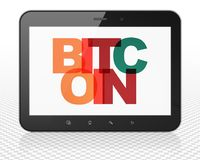 Cryptocurrency concept: Tablet Pc Computer with Bitcoin on  display. Cryptocurrency concept: Tablet Pc Computer with Painted multicolor text Bitcoin on display Stock Image
