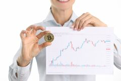 Cryptocurrency consultant holds bitcoin and graph with financial indicators in hands