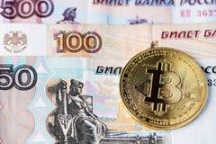 Cryptocurrency d'or de Bitcoin sur des billets de banque de roubles russes photos stock