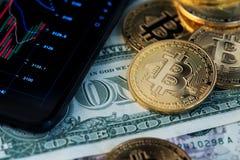 Cryptocurrency de Bitcoin et billets de banque d'un dollar à côté de téléphone portable image libre de droits