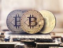 Cryptocurrency de oro en una placa de circuito del chip de ordenador, moneda electrónica, finanzas de Internet, tiro micro de Bit fotografía de archivo
