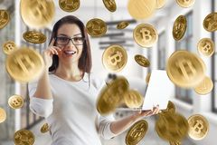 Cryptocurrency and e-commerce concept. Attractive smiling young businesswoman using laptop on abstract blurry interior background with golden bitcoin rain stock photography