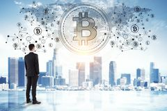 Cryptocurrency and e-commerce concept. Back view of young businessman on abstract city bitcoin background. Cryptocurrency and e-commerce concept royalty free stock photo