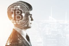 Cryptocurrency and e-commerce concept. Side portrait of handsome european businessman with bitcoin on abstract city background with copy space. Cryptocurrency stock images